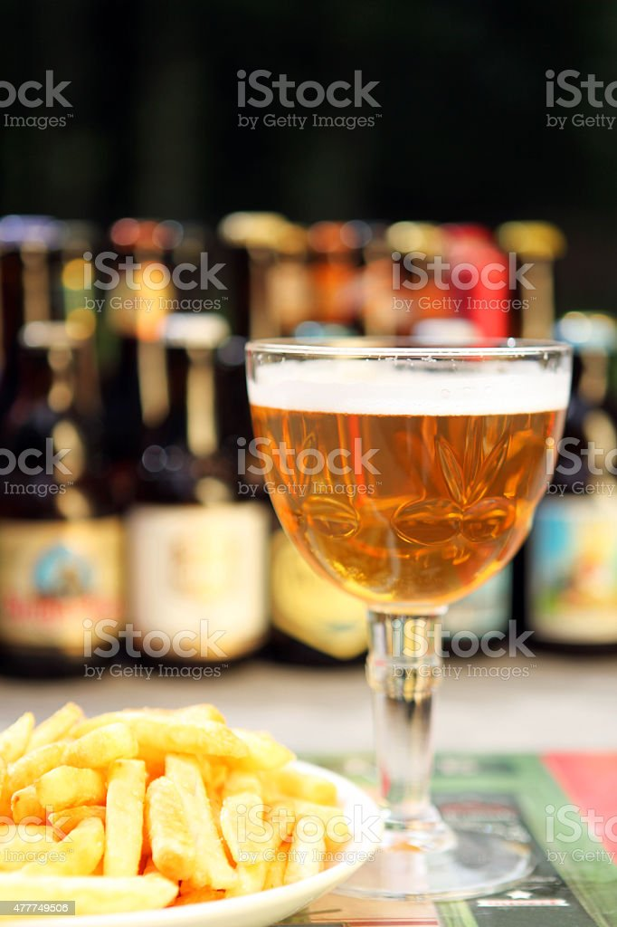 Belgian Beer Glass and Bottles and Traditional Belgian Fries stock photo