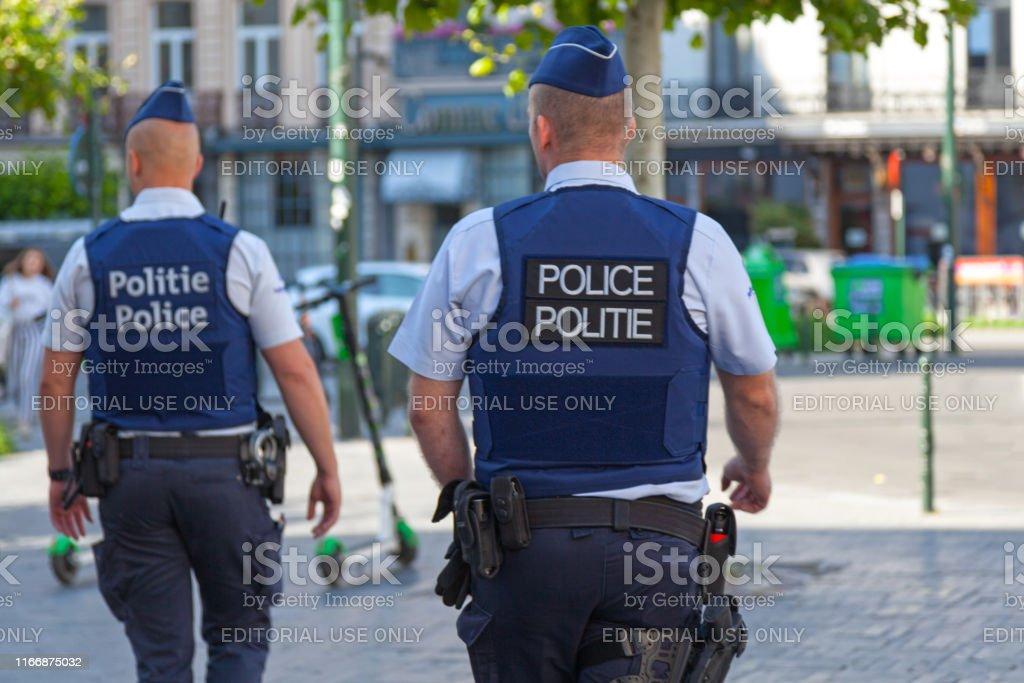 Belgian policemen in bulletproof vests Brussels, Belgium - July 03 2019: Policemen in bulletproof vest patrolling the street. Adult Stock Photo