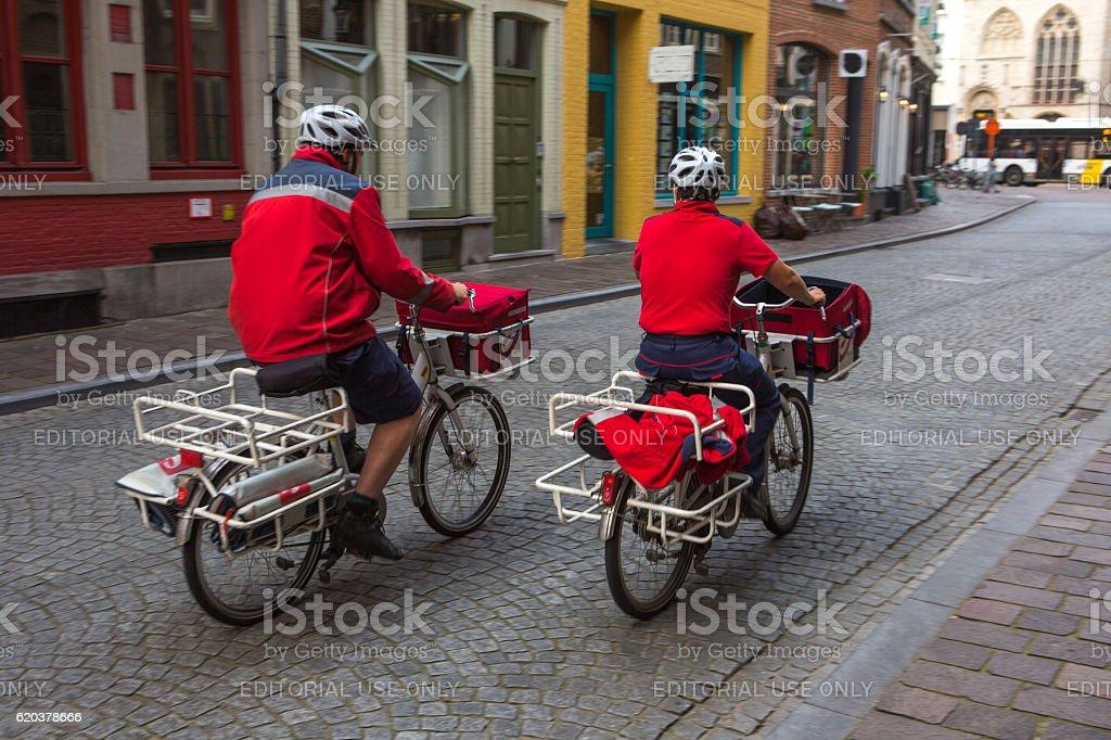 belgian postmen on bcycle at street of brugge belgium zbiór zdjęć royalty-free