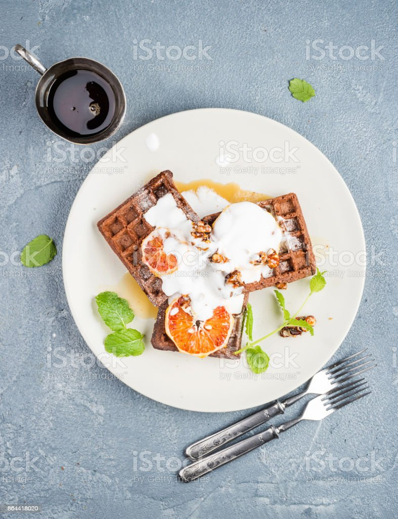 Belgian soft waffles with blood orange, cream, marple syrup and mint  on white plate stock photo