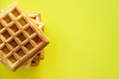 Belgian waffles heap on yellow background. Text space