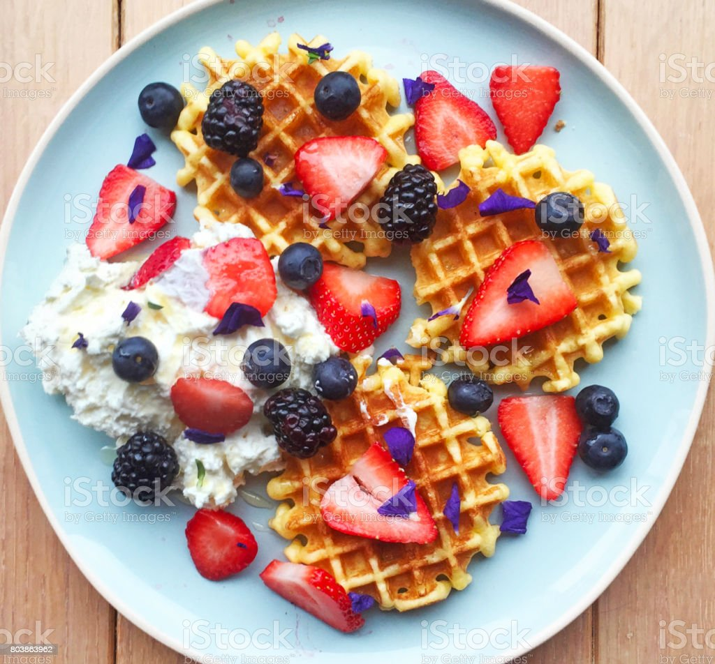 Belgian waffles topped with whipped cream, berries, syrup and edible flowers. Homemade breakfast aerial view on rustic wooden background. stock photo