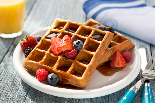Waffles with fruit on a rustic table top.