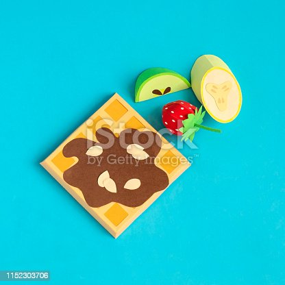 istock Belgian waffles with chocolate syrup and pieces of fruit made of paper 1152303706
