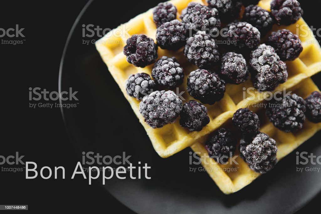 Belgian waffles with frozen blackberries on a black background, inscription bon appetit stock photo