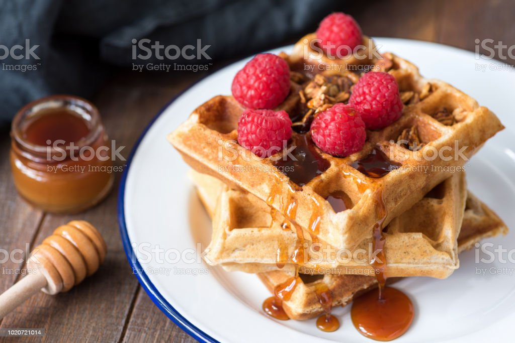 Belgian waffles with honey and berries on white plate stock photo