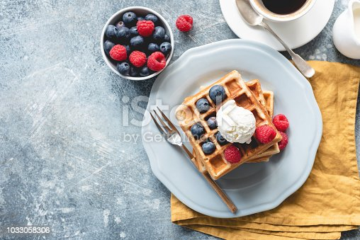 Belgian waffles with ice cream and berries on concrete background. Top view of sweet tasty breakfast. Copy space for your text