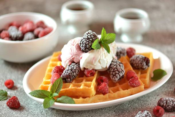 Belgian waffles with ice cream, mint and frozen raspberries and blackberries. Tasty breakfast. stock photo