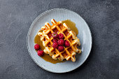 Belgian waffles with maple syrup and fresh raspberry. Grey slate background. Top view