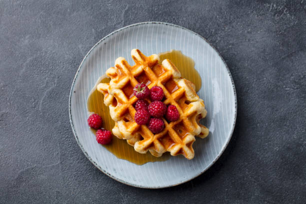 Belgian waffles with maple syrup and fresh raspberry. Grey slate background. Top view. Belgian waffles with maple syrup and fresh raspberry. Grey slate background. Top view waffle stock pictures, royalty-free photos & images