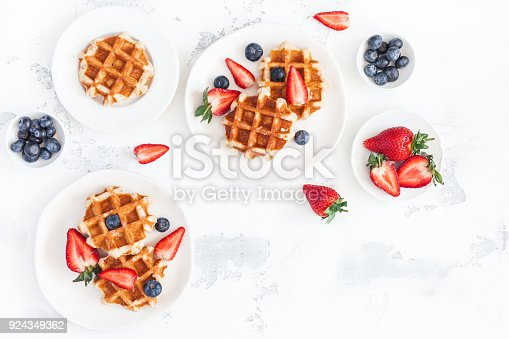 640978994 istock photo Belgian waffles with strawberry and blueberry. Flat lay, top view 924349362