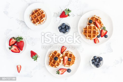 640978994 istock photo Belgian waffles with strawberry and blueberry. Flat lay, top view 934707186