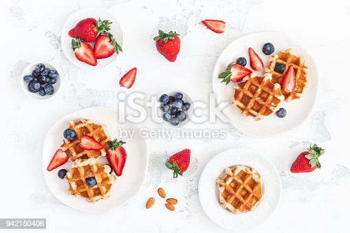 640978994 istock photo Belgian waffles with strawberry and blueberry. Flat lay, top view 942150406