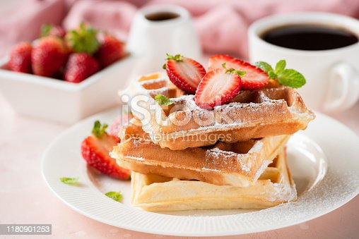Belgian waffles with strawberry and powdered sugar on white plate, pink background