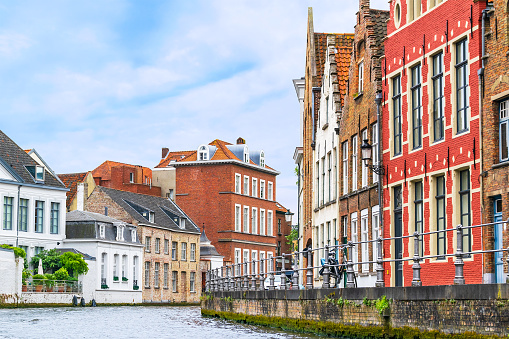 Belgium, Bruges. A street along the canal with old houses along the canal.