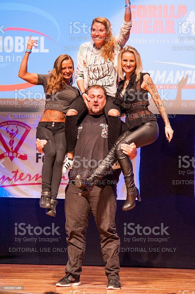 Belgium strongman Jimmy Laureys lifts girls on stage stock photo