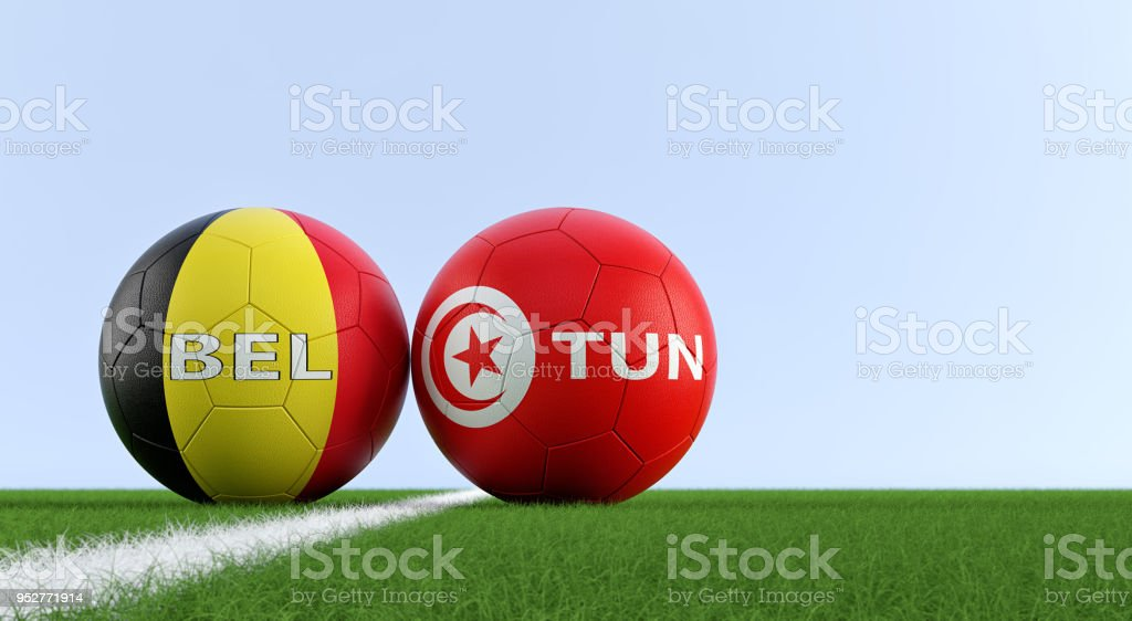 Belgium vs. Tunisia Soccer Match - Soccer balls in Belgiums and Tunisias national colors on a soccer field. stock photo