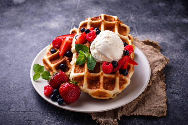 Belgium waffles with berries and ice cream Belgium waffles with berries and ice cream. Selective focus waffle stock pictures, royalty-free photos & images
