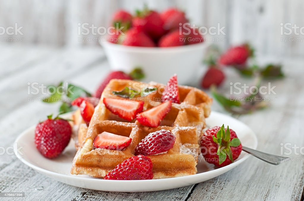 Belgium waffles with strawberries and mint on white plate stock photo