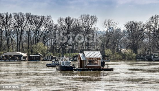 Belgrade, Serbia, March 17th 2016: Police boat patrols making effort to take control of an undocked raft house freely floating down the Sava River.