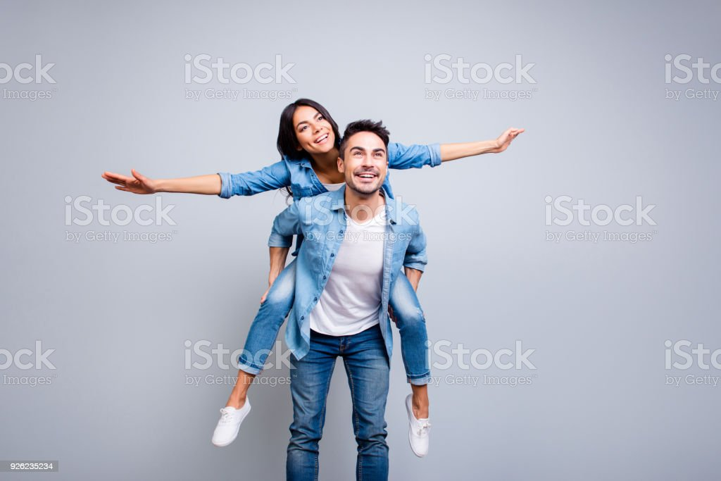 I believe I can fly. Love story of attractive, funny, cheerful couple - handsome man carrying his lover on back like plane, woman opens her hands to the side over grey background royalty-free stock photo