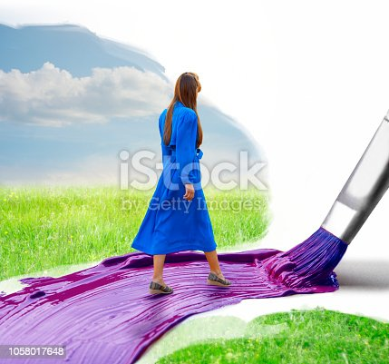 Young woman walking on a painted path and the huge brush paints that path while she is walking forward. Believe in yourself concept.