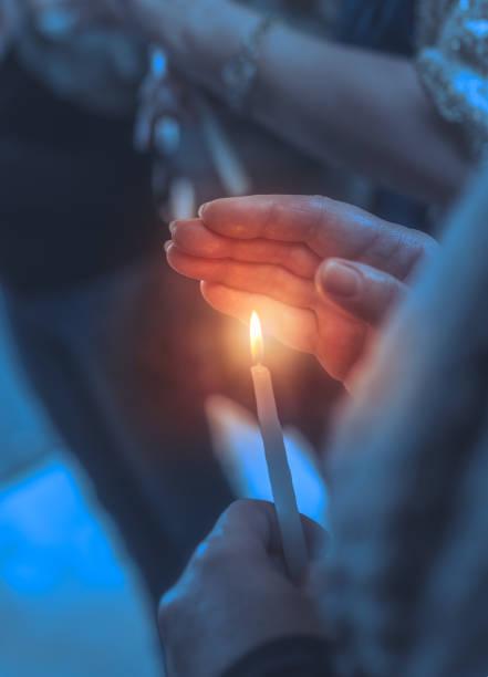 gläubige in einer kirche mit kerze - osterfeuer stock-fotos und bilder
