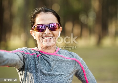 Shot of a smiling mature woman in sportswear taking selfie after exercising outdoors