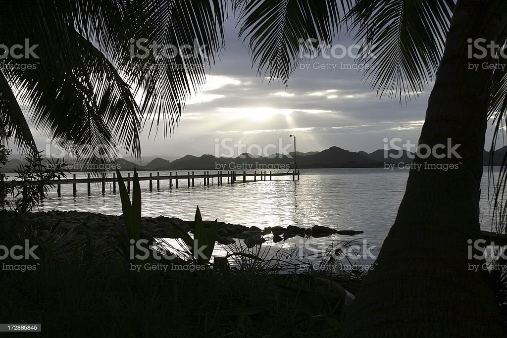 "Belize Southern Lagoon Cloud Palm Pier ""Sunset through clouds; pier at Manatee Lodge, Southern Lagoon, Belize."" Back Lit Stock Photo"