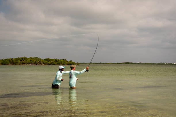 A Belizean fishing guide pointing out the school of bonefish to the  fly fisherman.