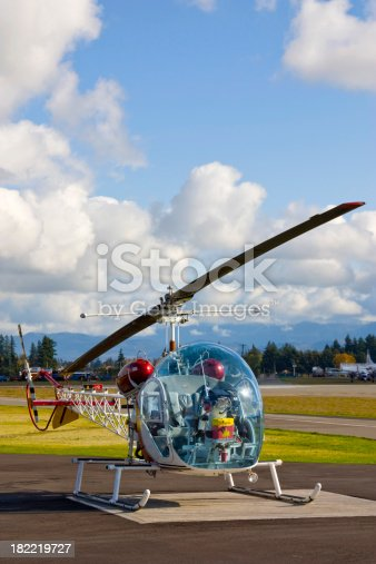 A restored Bell 47 helicopter sitting in the sunshine