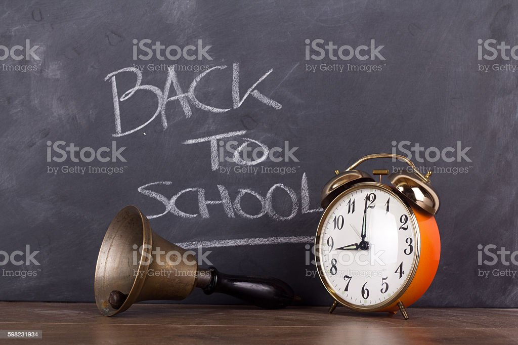 Bell and alarm clock against a blackboard foto royalty-free