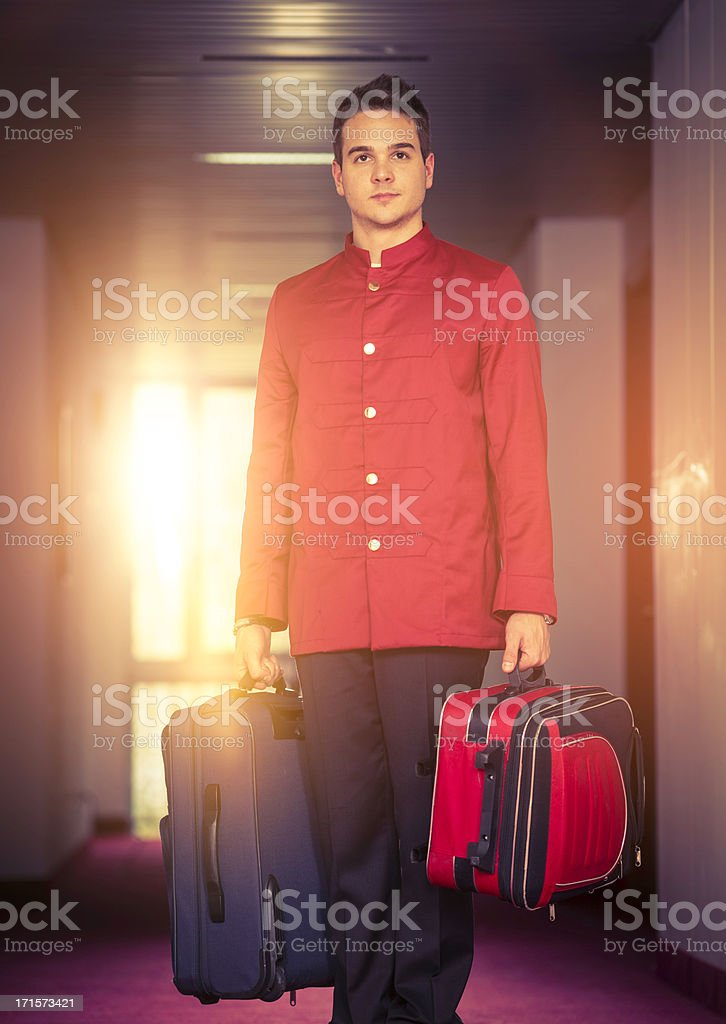 Bell boy carrying luggage stock photo