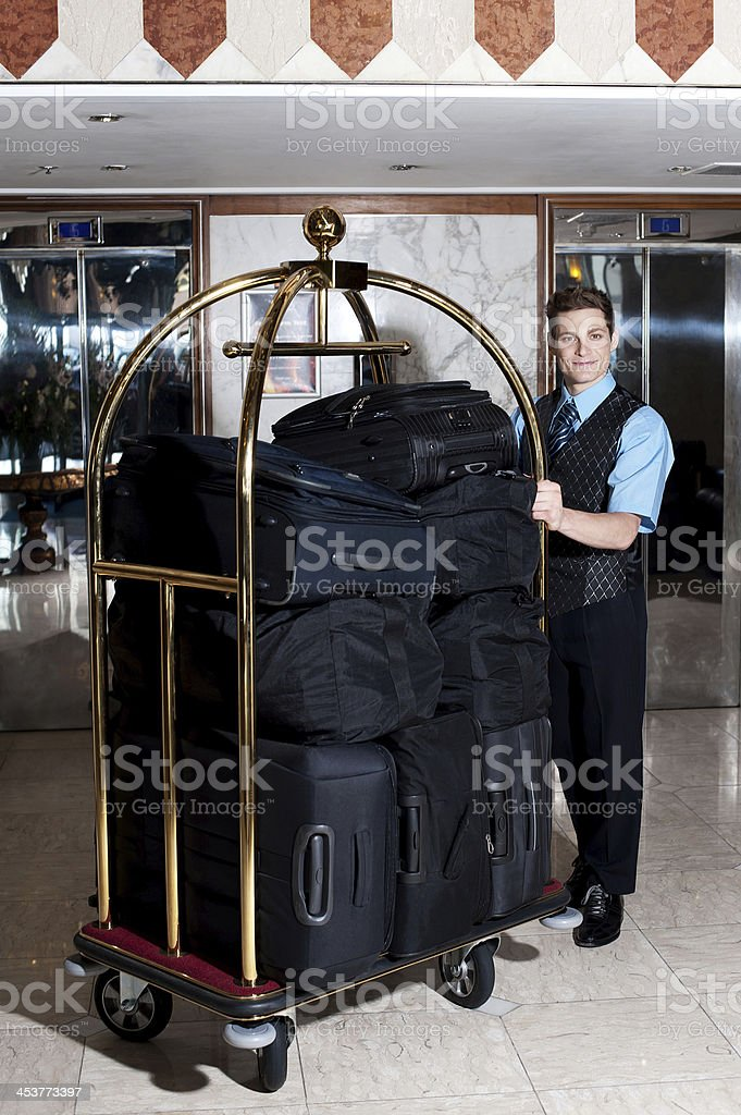 Bell boy pushing cart loaded with luggage stock photo