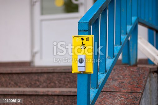 Bell button to call staff for wheelchair users near the pharmacy stairs