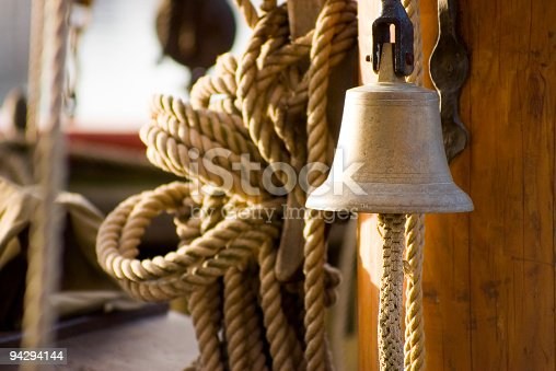 Atmospheric brass ships bell against wooden mast with natural fibre ropes and wooden tackle blocks. Adobe RGB 1998 color profile.