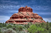 Bell Rock, a popular scenic landmark south of Sedona, Arizona with clouds and blue sky and green trees and green bushes.