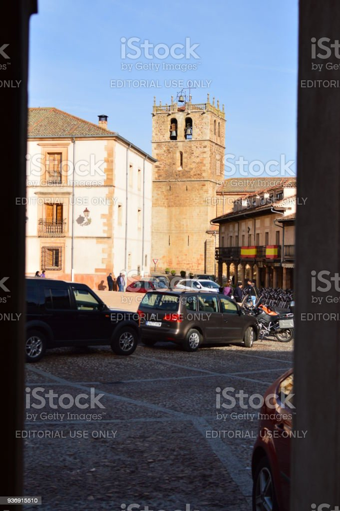 Bell Tower Of The Church In Town Square Of Riaza Cradle Of The Red Villages Besides Beautiful Medieval Town In Segovia. Architecture Landscapes Travel Rural Environment. stock photo