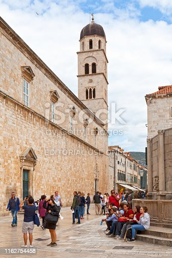 Dubrovnik, Croatia - April 18 2019: Tourists walking next tot the bell tower of the Franciscan Church of the Little Brothers on the Stradun.