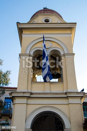 Bell tower in Athens with the Greek flag on it.