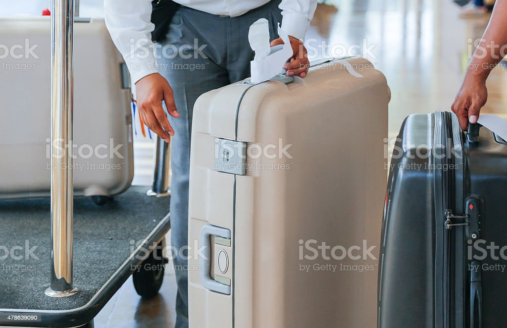 Bellboy carrying heavy luggage in luxury hotel stock photo