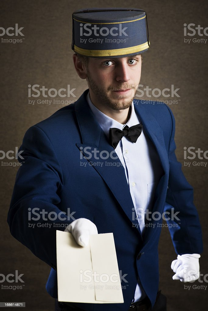 Bellboy holding an envelope as copy space stock photo