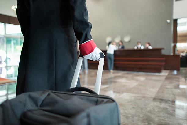 Bellboy pulling bag through the hotel - foto de stock