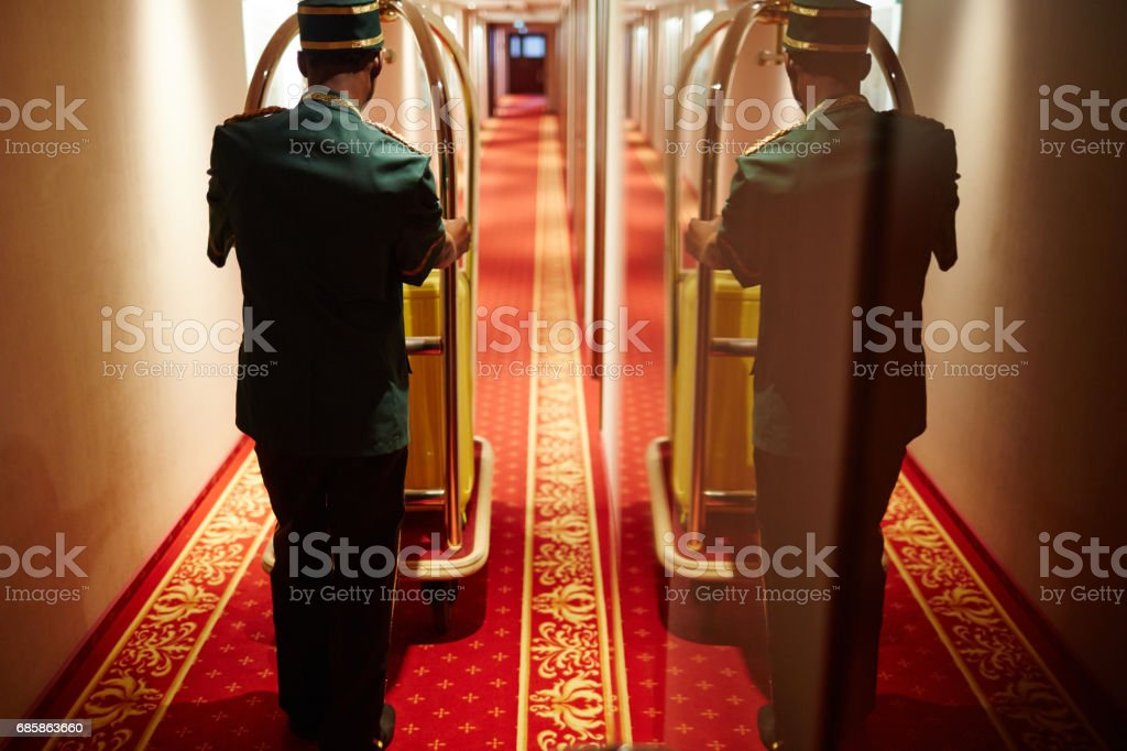 Bellboy Pushing Luggage Cart in Hotel Hallway stock photo