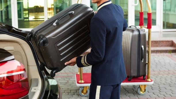 Botones llevando equipaje de huéspedes de ti coche a su habitación - foto de stock
