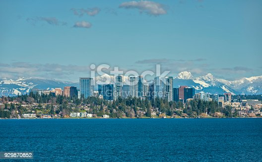 The Snow Capped Cascade Mountain Range stand Tall Behind the City of Bellevue, Washington and Lake Washington on a Sunny and Blue Afternoon