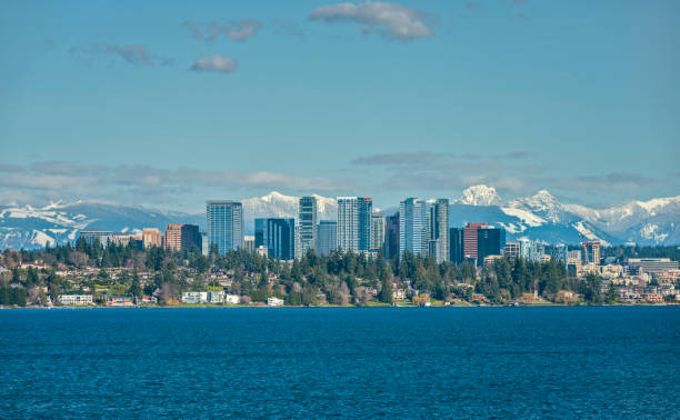 Bellevue, Washington and Cascade Mountains over Lake Washington The Snow Capped Cascade Mountain Range stand Tall Behind the City of Bellevue, Washington and Lake Washington on a Sunny and Blue Afternoon washington state stock pictures, royalty-free photos & images
