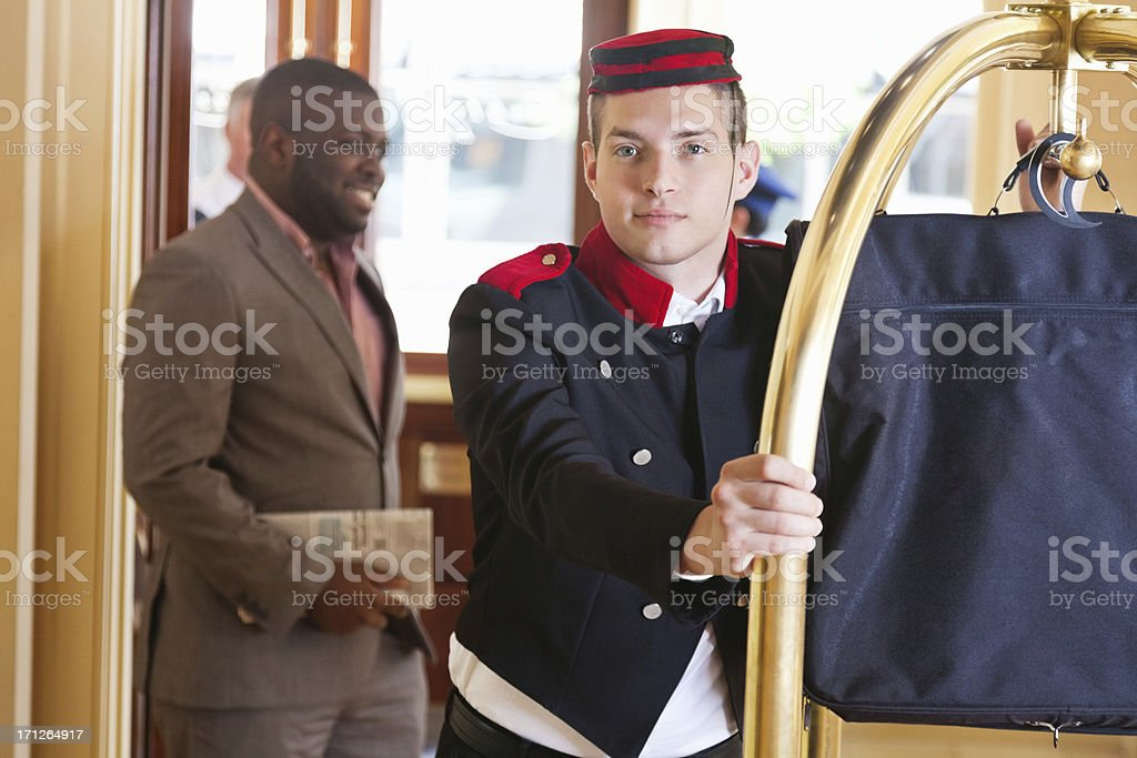 Bellhop moving luggage on cart for hotel guest stock photo