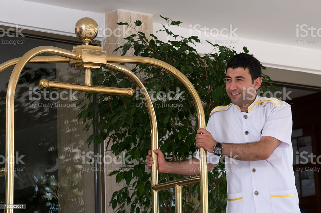 A bellhop pushing the clothes trolley stock photo