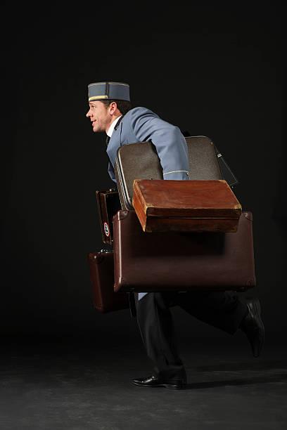 Bellhop corriendo con valijas - foto de stock
